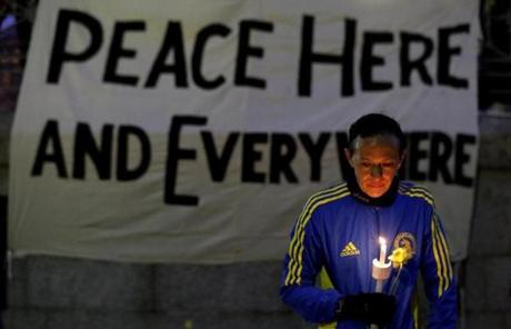 Lizzie Lee, 56, of Lynwood, Wash., who had participated in her first Boston Marathon, holds a candle and a flower at