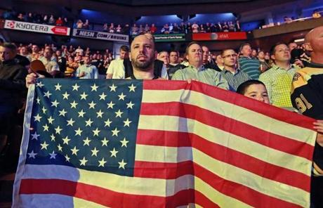 Mike Adler (left) and his 10 year old son Gabe of Framingham held an American flag during the moment of silence before the Bruins game Wednesday.