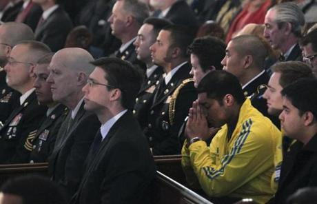 A man in a Boston Marathon jacket bowed his head as he waited for the service to begin.
