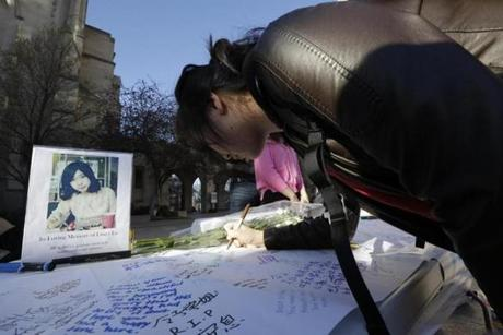 A photograph of Boston University graduate student Lingzi Lu sat next to a message board outside the school's Marsh Chapel on Wednesday.