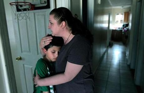 Michelle Blain comforted her son, 10-year-old Louie Blaine-Santos, at their home in Watertown.