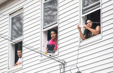 Residents watched police in front of a building in Watertown.