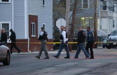 Officials at a crime scene in Watertown. No cars were allowed in or out of the twon Friday morning.