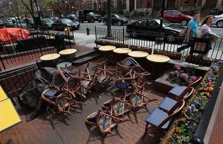 Chairs at a restaurant on Newbury Street were blown over by the wind. The street and restaurant normally are crowded with people.