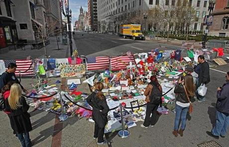 The memorial at the intersection of Boylston and Berkeley streets had a few visitors during the lockdown Friday.