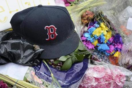 A Red Sox hat and flowers were at a memorial near Fenway.