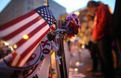 People gathered at a makeshift memorial for victims near the site of the Boston Marathon bombings at the edge of the still-closed section of Boylston Street.