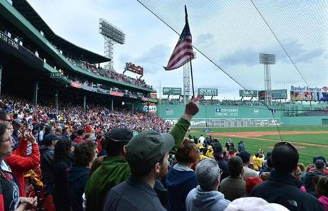 A Red Sox fan held a flag during the broadcast of a memorial program.