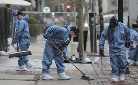 Workers cleaned up at the site of the first Boston Marathon bombing on Boylston Street, scrubbing away on Tuesday.