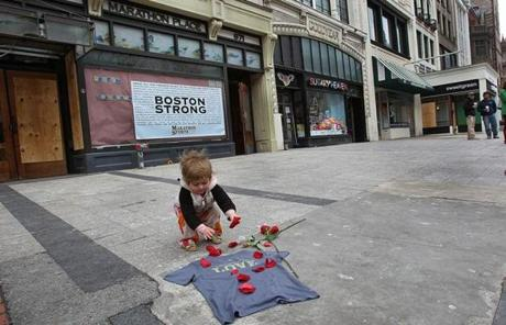 A young girl placed rose petals on the site of the first bombing on Boylston Street on Wednesday.