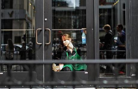 A Starbucks employee cleaned the windows of the store on Boylston Street.