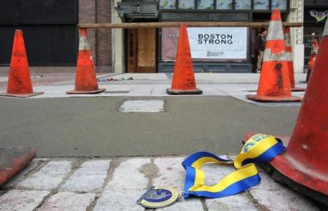 A marathon medal was placed near the rebuilt sidewalk at the site of the first bombing.