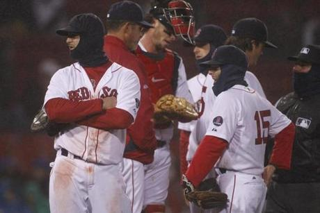 Red Sox players had to wait as the field was manicured during a delay for wetness in the sixth inning.