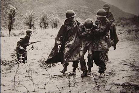 Captain Emil J. Kapaun, right, helped to carry an exhausted soldier off a battlefield in Korea in November 1950.