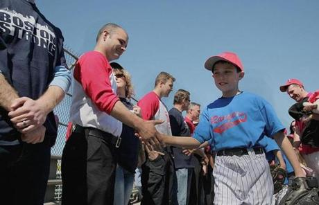 Nine-year-old Nolan McKenna greeted Boston police and firefighters who lined Savin Hill Avenue. McKenna was a friend and teammate of Richard's.