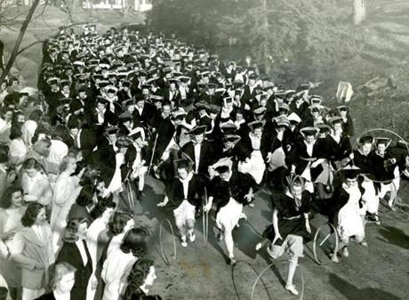 May 1, 1939:  Seniors ran down Tupelo Lane during the hoop rolling race. The Wellesley Class of 1895 started the tradition with the understanding that the fastest hoop roller would become the first bride of the graduating class. In 1939, Ned Read president of the Harvard Lampoon, wearing a wig, disguised himself as a Wellesley coed and won the race. Once discovered, the Wellesley seniors pushed him into Lake Waban, starting another tradition which has continued for any male interlopers through the years.