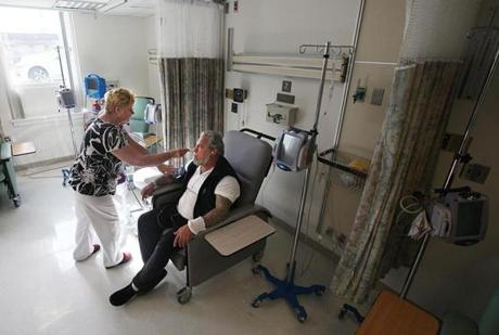 "Scott ""Scoot"" Caseau got intravenous antibiotics for his Lyme disease and related illnesses at Cape Cod Hospital, while nurse Rita Thornton checked his vitals."