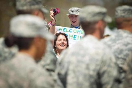 5/02/2013 - Reading, MA - Kathy Anderson, cq, of North Reading, shouted to her nephew, Kaulin Trainor, cq. At right is Devan Hawk, cq, 12, of Palmer, MA, who was greeting his father. Approximately 130 soldiers from the 972nd Military Police Company returned to the joyous cheers of friends and family at Camp Curtis Guild in Reading on May 2, 2013 after a nine-month mobilization in Qatar to perform force protection missions in support of Operation Enduring Freedom. This is the third overseas deployment of the 972nd since 9/11/2001. The unit previously deployed to Uzbekistan and Pakistan in 2002-2003, and to Iraq in 2007-2008. The unit also performed security support at Logan International Airport in 2001-2002; security support for the Democratic National Convention in Boston in 2004; and soldiers of the 972nd served in Louisiana during Hurricane Katrina response operations in 2005. Item: 03homecomingphoto. Dina Rudick/Globe Staff