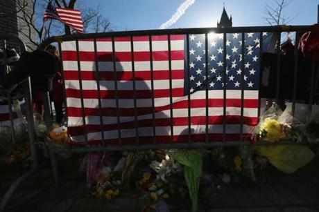 A person's shadow was cast against an American flag at a memorial for the victims of the Boston Marathon bombings in Copley Square.