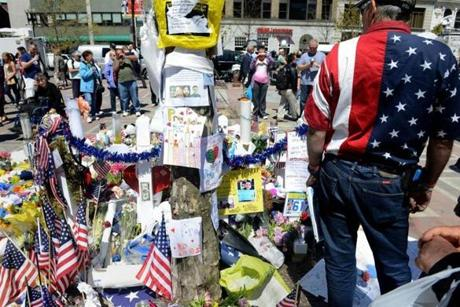 A man with an American flag shirt stood at the memorial site in Copley Square.