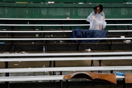 LOUISVILLE, KY - MAY 04: Race fans sit in the rain prior to the 139th running of the Kentucky Derby at Churchill Downs on May 4, 2013 in Louisville, Kentucky. (Photo by Rob Carr/Getty Images)