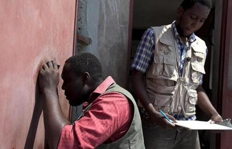 The Boston resident (not pictured) also taught security techniques and courses on how to manage aggressive behavior. Gervais Rosmey (left) peered through a peephole to look at an incoming visitor at the Partners in Health offices in Port-au-Prince.
