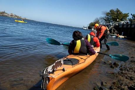Plum Island Kayak owner Ken Taylor (standing) helped guests Yoonn Cho (left) and Lars Anders launch their kayak into the water.