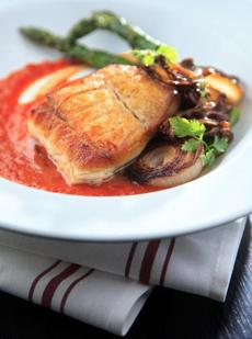 Roasted halibut with mushrooms, asparagus, charred onions, and a tomato sauce redolent of ginger.