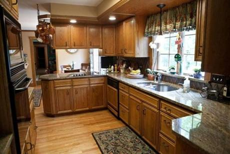 The wholly updated kitchen has light brown granite counters and oak cabinets as well as a built-in china cabinet.