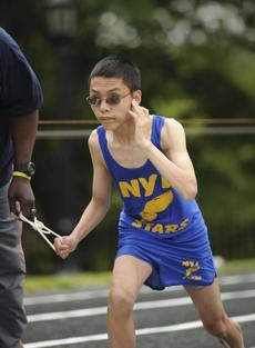 Kevin Cao with the New York Institute of Special Education covered one ear so he could listen to the instruction from an official telling them to start the 400 x 4 race.