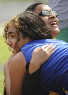 The New York Institute for Special Education's Kelsey Lora (left) hugged teammate Angela Villota after finishing her long throw tries.