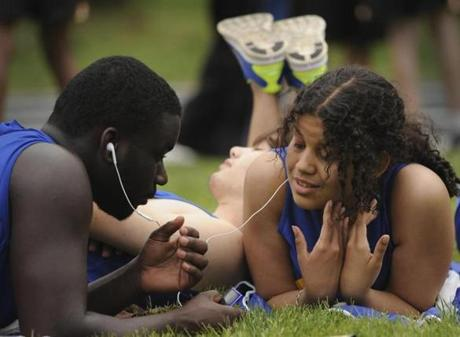 Andre Hopkins (left) and Victoria Vergara listened to music while sharing earbuds as teammate Edward Donnelly caught a nap. The trio are from the New York Institute for the Special Education.