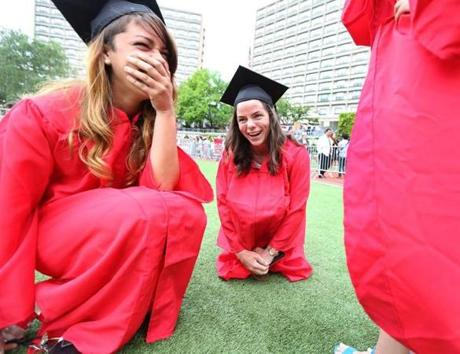 While waiting for friends after Boston University graduation ceremonies at Nickerson Field, sailing team members Tori Pinheiro (left) and Cristina Wiley used their gowns to shield their legs from the cold.