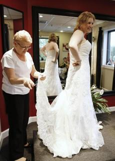 Valerie Gayeski fits a gown for Erin Golden, whose wedding plans had to be revised, at Peabody's Blushing Bride.