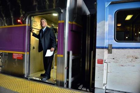 A conductor watched from the door as the train departed South Station and began its journey to Hyannis.
