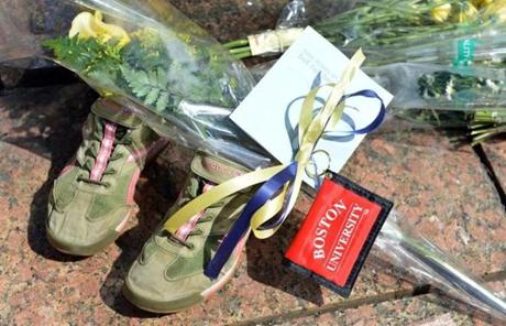 A pair of running shoes, flowers, and a Boston University key chain at a makeshift memorial.