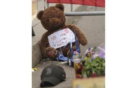 A Teddy bear wiht a sign saying,