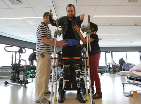 William Lautzenheiser, who lost all four limbs due to an infection, transitioned to a standing position from his wheelchair at Spaulding Rehabilitation Hospital. He is considering a double arm transplant and, possibly in the future, a leg transplant.