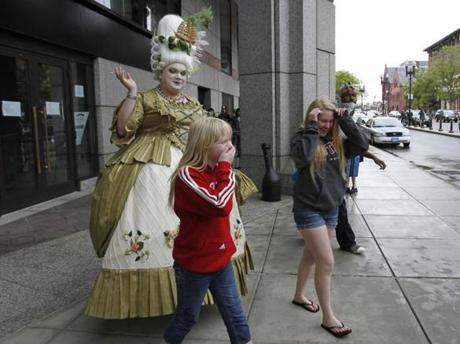 Corry Ledebur, 10, of Pennsylvania (center) reacted to Eric Boble (left), who is dressed as Marie Antoinette outside of Anime Boston.