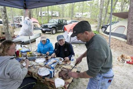 Russell St. Don cut up steaks for Kerri Masapollo (left), Marge Bremilst (center), and Joseph St. Don, at their campsite at Indianhead Resort. The campers hail from Fairhaven.