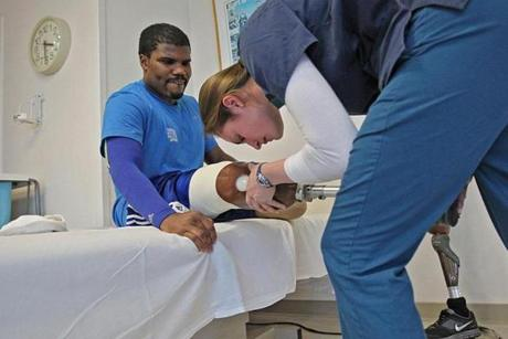 "Muji Karim with physical therapist Alyson Jodoin. He has been determined to keep working hard. ""I can do everything about how I feel, how I react, and how hard I work to get back on my feet,"" he said."