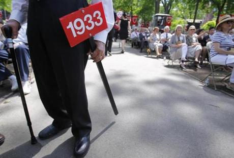 Harvard alumnus Clarence Agress held the sign for his class of 1933 during the afternoon commencement procession at Harvard University in Cambridge.
