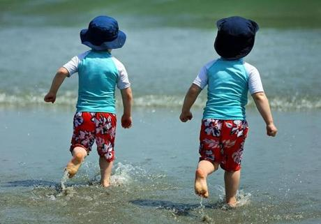 Twins Cody and Connor Zinkus, 3, of Framingham ran in the cool water at Nantasket Beach in Hull.