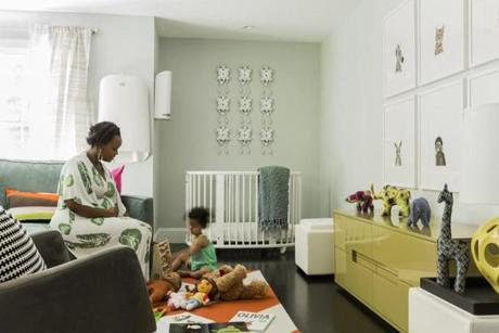 "Kibibi Ganz and her 2-year-old daughter, Eva, enjoy playtime in the nursery, painted Benjamin Moore ""Sterling,"" brightened with colorful furnishings."