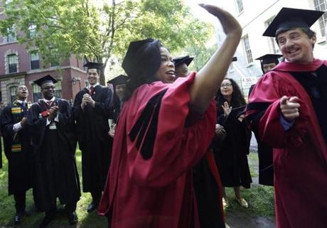Winfrey held her hand up to high-five graduates as she walked during the procession.