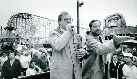 June 12, 1985: After the close of Paragon Park, David Norton (left) and Doc Horton conducted the auction of the roller coaster at Paragon Park. The final bidder was Mark Mason of Wild World of Landover, Maryland. He can be seen in the bottom right of the photo under the hand of Doc Horton wearing the white shirt and black coat with his arms crossed. He bought the coaster with the top bid of $28,000.