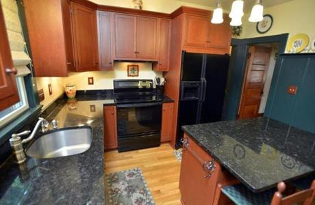 The updated kitchen has a prep island, black granite counters, Shaker-style cherry cabinets, and tall wainscoting.