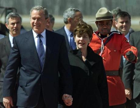 U.S. President George W. Bush and his wife Laura, are escorted by a Canadian mountie and the new U.S. ambassador to Canada, Paul Cellucci (back left), after stepping down from Air Force One at the Quebec City airport upon arrival to attend the third Americas Summit, April 20, 2001. The heads of 34 Western Hemisphere nations will meet from April 20-22 to discuss the creation of a free trade zone. REUTERS/Jim Bourg