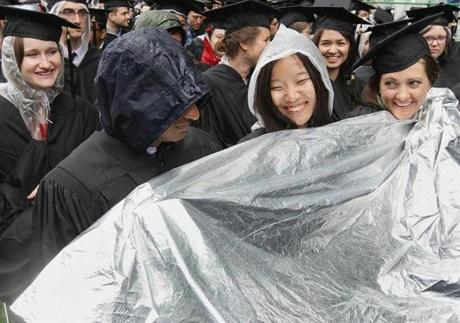 Cambridge, MA 060713 Urban planning graduate students Tushar Kansal (cq), Zheng Jia (cq) and Carri Hulet (cq) huddled together during MIT's commencement in Cambridge, Friday, June 7 2013. (Staff Photo/Wendy Maeda) section: Metro slug: 08MIT reporter:
