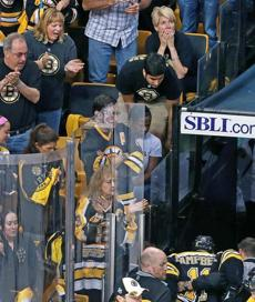 Appreciative Bruins fans watch as Gregory Campbell is helped down the tunnel after breaking his leg.